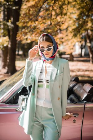 Photo for Stylish woman in sunglasses looking at camera near vintage car outdoors - Royalty Free Image