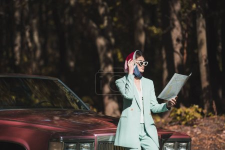 Stylish woman in sunglasses looking at map near car outdoors