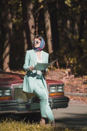 Photo pour Femme élégante dans les lunettes de soleil tenant carte près de vintage auto - image libre de droit
