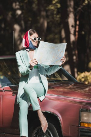 Photo for Fashionable woman in sunglasses holding map near bumper of vintage auto - Royalty Free Image