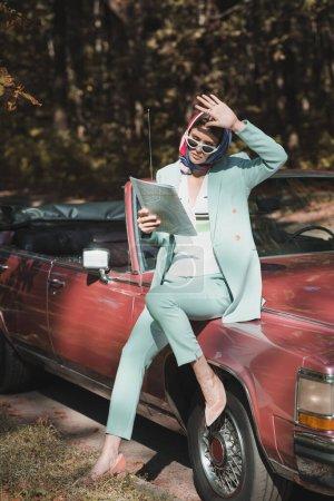 Photo pour Femme élégante souffrant de la lumière du soleil tout en tenant la carte près de la voiture à l'extérieur - image libre de droit