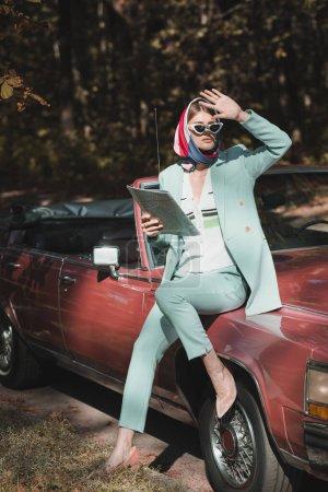 Photo pour Femme élégante en lunettes de soleil tenant la carte et regardant loin près de voiture vintage sur la route - image libre de droit