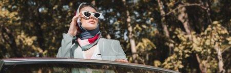 Stylish woman touching sunglasses near car outdoors, banner