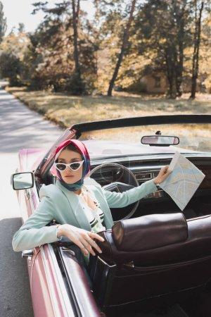 Photo pour Femme élégante tenant carte tout en étant assis sur le siège du conducteur de voiture cabriolet sur la route - image libre de droit