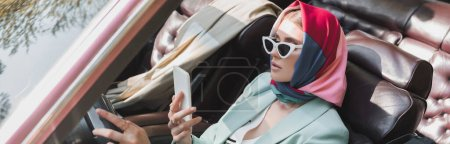 Fashionable woman using smartphone while driving cabriolet car on blurred foreground, banner