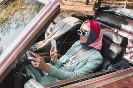 Photo for Elegant woman using smartphone while driving roofless car on blurred foreground - Royalty Free Image