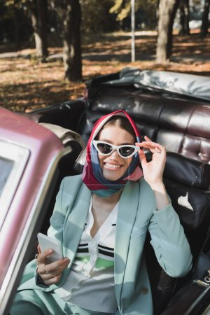 Smiling woman touching sunglasses while holding smartphone in cabriolet car