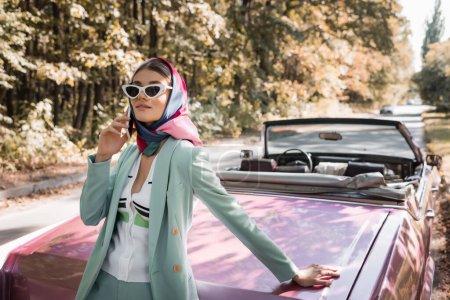 Photo for Elegant woman talking on smartphone near retro car on road during trip - Royalty Free Image