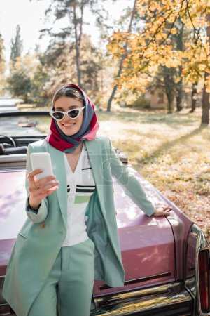 smiling, fashionable woman looking at smartphone while standing near vintage cabriolet