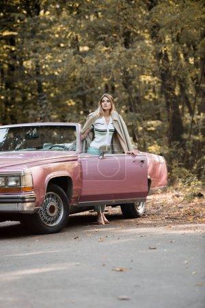 mujer joven mirando hacia otro lado mientras está de pie cerca de la puerta abierta del cabriolet en el borde de la carretera