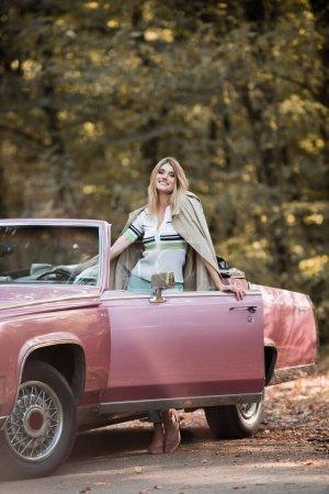 femme excitée regardant la caméra tout en se tenant près de la porte ouverte de la voiture convertible