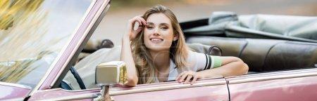 Photo pour Femme joyeuse tenant la main près de la tête tout en regardant la caméra de cabriolet, bannière - image libre de droit
