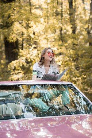 fröhliche Frau schaut weg, während sie Karte im Cabriolet hält