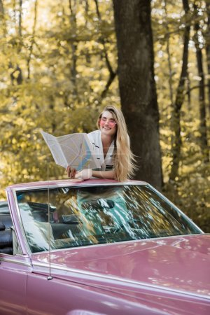 smiling woman in sunglasses looking at road atlas while sitting in cabriolet in forest