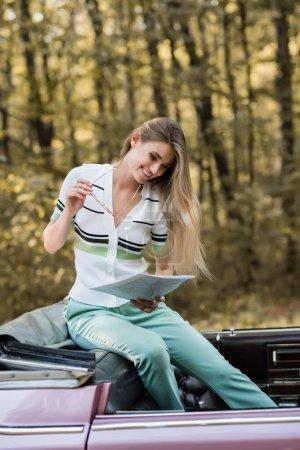 Lächelnde Frau, die im Cabrio mit Sonnenbrille auf den Straßenatlas blickt