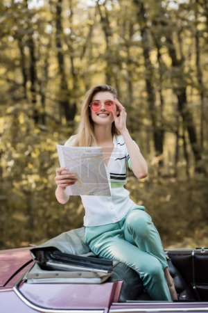 cheerful woman touching sunglasses and looking at camera while holding map in cabriolet