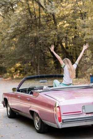 back view of young woman sitting in vintage convertible car with hands in air