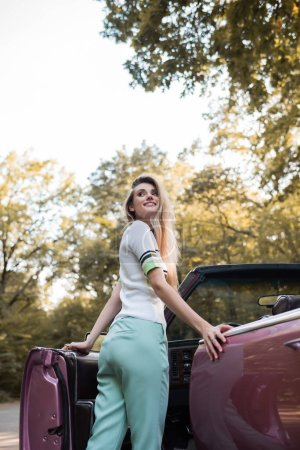 cheerful young woman looking away while opening door of vintage cabriolet