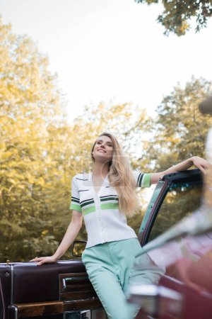 Photo pour Vue à angle bas de la femme souriante regardant loin tout en se tenant près de la porte ouverte du cabriolet sur le premier plan flou - image libre de droit
