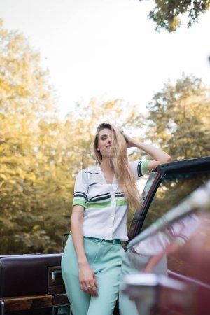 Photo pour Femme élégante touchant les cheveux et regardant la caméra tout en se tenant près de la porte ouverte de cabriolet sur le premier plan flou - image libre de droit