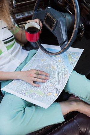 Ausgeschnittene Ansicht einer Frau mit Karte und Tasse Kaffee im Auto