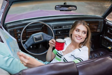 Photo for Joyful woman looking away while holding coffee and road atlas in cabriolet on blurred foreground - Royalty Free Image
