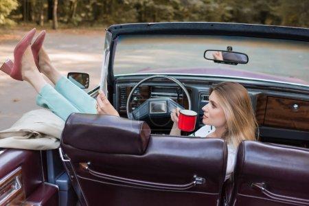 Frau legt Beine auf Tür, während sie Tasse Kaffee im Cabriolet hält