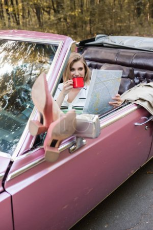 Photo for Smiling woman drinking coffee and looking at map while putting legs on rear view window on blurred foreground - Royalty Free Image