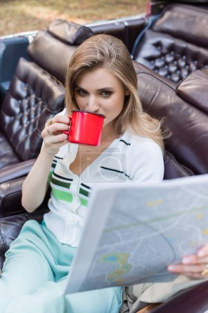 young woman drinking coffee while looking at map in cabriolet on blurred foreground