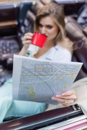 Photo pour Jeune femme regardant atlas de la route et boire du café tout en étant assis dans le cabriolet sur fond flou - image libre de droit