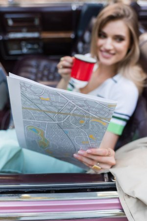 smiling woman holding map and cup of coffee while sitting in cabriolet on blurred background