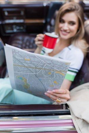 femme souriante tenant carte et tasse de café assis dans le cabriolet sur fond flou