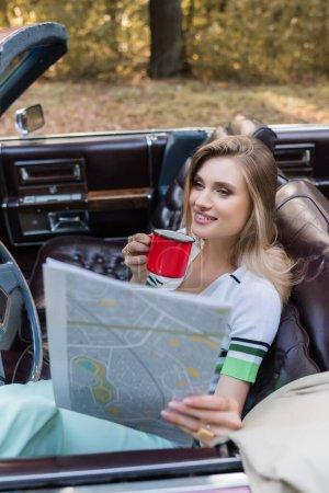 Lächelnde Frau mit Kaffee in der Hand und Blick auf Landkarte im Cabriolet im verschwommenen Vordergrund