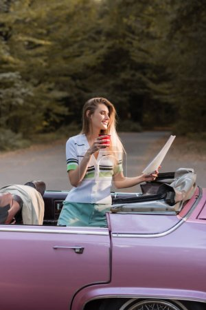 happy woman holding map and cup of coffee while standing in convertible car