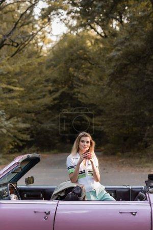 Photo pour Jeune femme regardant la caméra tout en tenant une tasse de café dans le cabriolet sur la route près de la forêt - image libre de droit