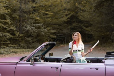 Photo for Young woman looking away while standing in cabriolet with map and cup of coffee - Royalty Free Image