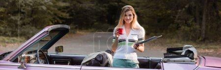 lächelnde Frau, die in die Kamera blickt, während sie Straßenatlas und Kaffeetasse im Cabrio hält, Banner