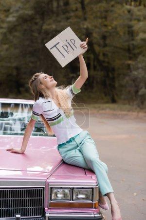 Photo pour Femme souriante tenant une pancarte avec lettrage de voyage tout en étant assis sur le capot de cabriolet - image libre de droit