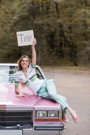 stylish young woman holding placard with trip lettering while lying on cabriolet hood