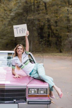 Photo pour Élégant jeune femme tenant plaque avec lettrage voyage tout en étant couché sur capuche cabriolet - image libre de droit