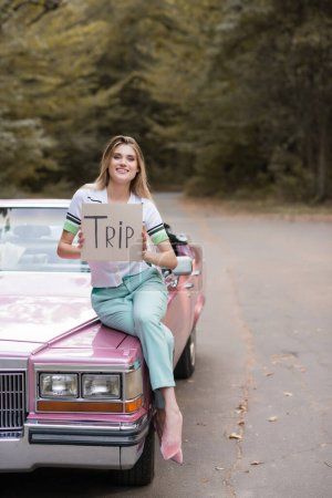 Photo pour Femme élégante souriante regardant la caméra tout en étant assis sur le capot cabriolet - image libre de droit