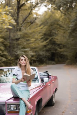 Photo for Smiling woman looking at camera while sitting on hood of cabriolet and holding book - Royalty Free Image