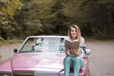 Photo for Happy young woman reading book while sitting on hood of convertible car on blurred background - Royalty Free Image