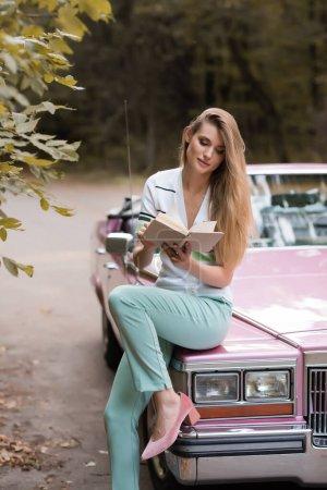 Photo pour Élégant livre de lecture femme tout en étant assis sur le capot de cabriolet vintage - image libre de droit