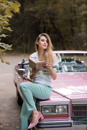 Photo for Young woman looking away while sitting on hood of retro cabriolet and holding book on blurred background - Royalty Free Image