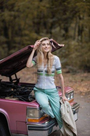Photo pour Femme souriante toucher les cheveux et regarder loin tout en étant assis sur une voiture cassée avec capuche ouverte - image libre de droit