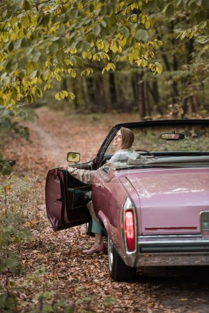 young woman in coat opening door while sitting in vintage cabriolet