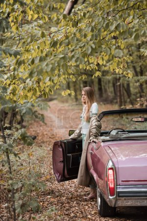 stylish woman looking away while standing near open door of cabriolet in forest