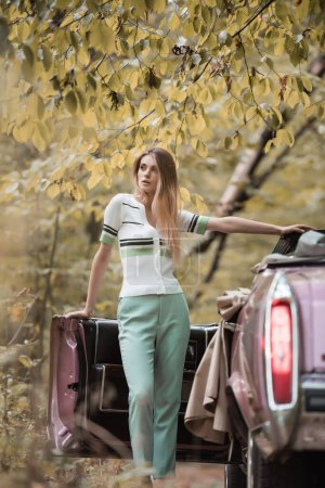 young woman looking away while standing near open door of cabriolet on blurred foreground