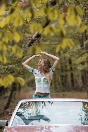 femme excitée dans des lunettes de soleil regardant loin tout en se tenant les mains au-dessus de la tête en cabriolet